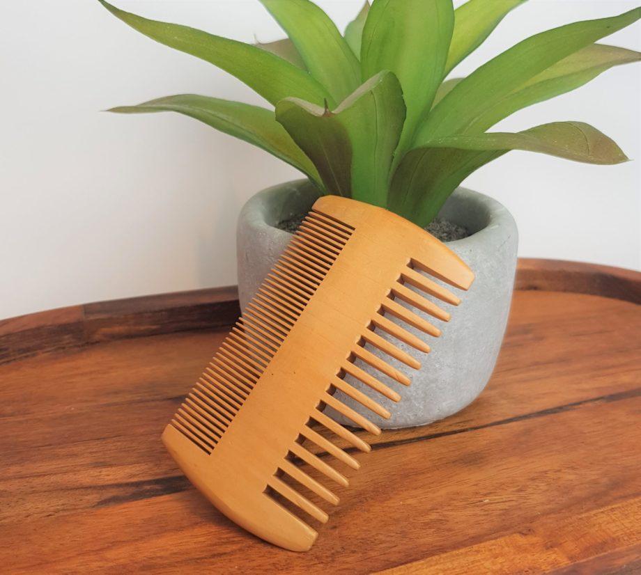 beard comb against plant on wood