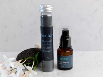 activated-charcoal-facial-scrub-and serum with pumice on marble