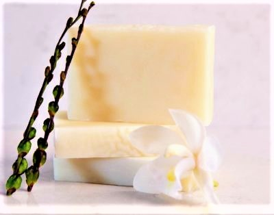 manuka honey soap three in a stack with orchid and plant on marble background