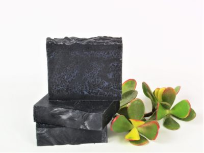 three charcoal and rose geranium soaps in a stack next to plant on a white background