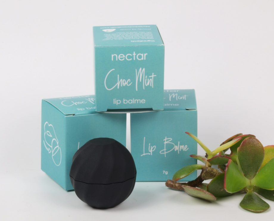 black round lip balm in container in front of individual gift boxes