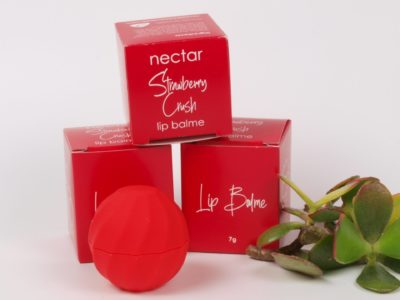 red lip balm in container in front of individual gift boxes