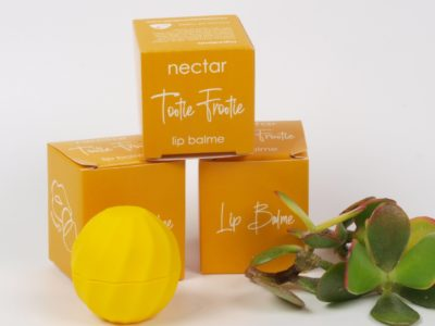 ellow lip balm in container in front of yellow gift boxes