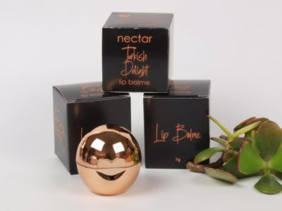 Lip Balm in rose gold container in front of black boxes