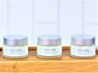 Viso day face moisturiser in glass pots on wood with white brick background