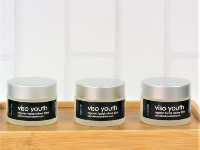 Viso Youth moisturisers in glass pots with silver lids on wood base