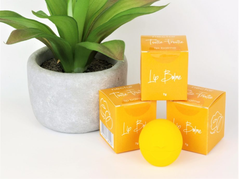 lip balm tootie footies smooth ball with plant and boxes