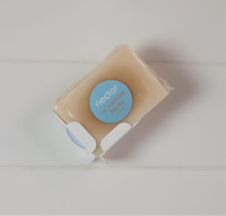 manuka honey labelled soap in white block dock attached to white tiled wall