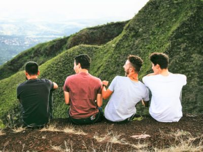 group of men on mountain laughing and looking at view