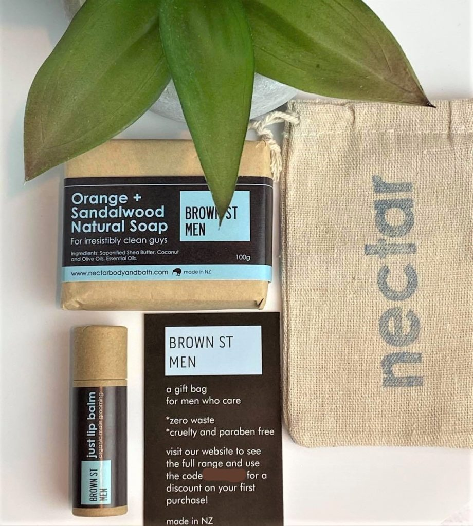 contents of man bag with plant in background in flatlay